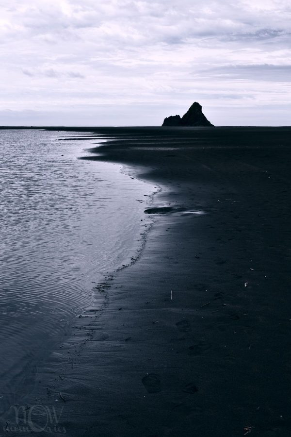 Karekare black sand beach rock coast sea in a cloudy day